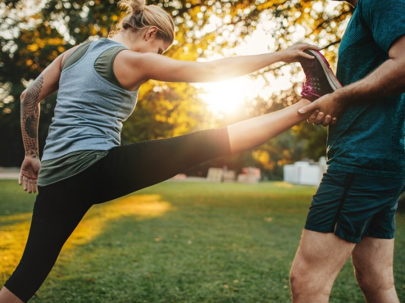Male,Coach,Helping,Young,Woman,Exercising,In,Park.,Trainer,Helping